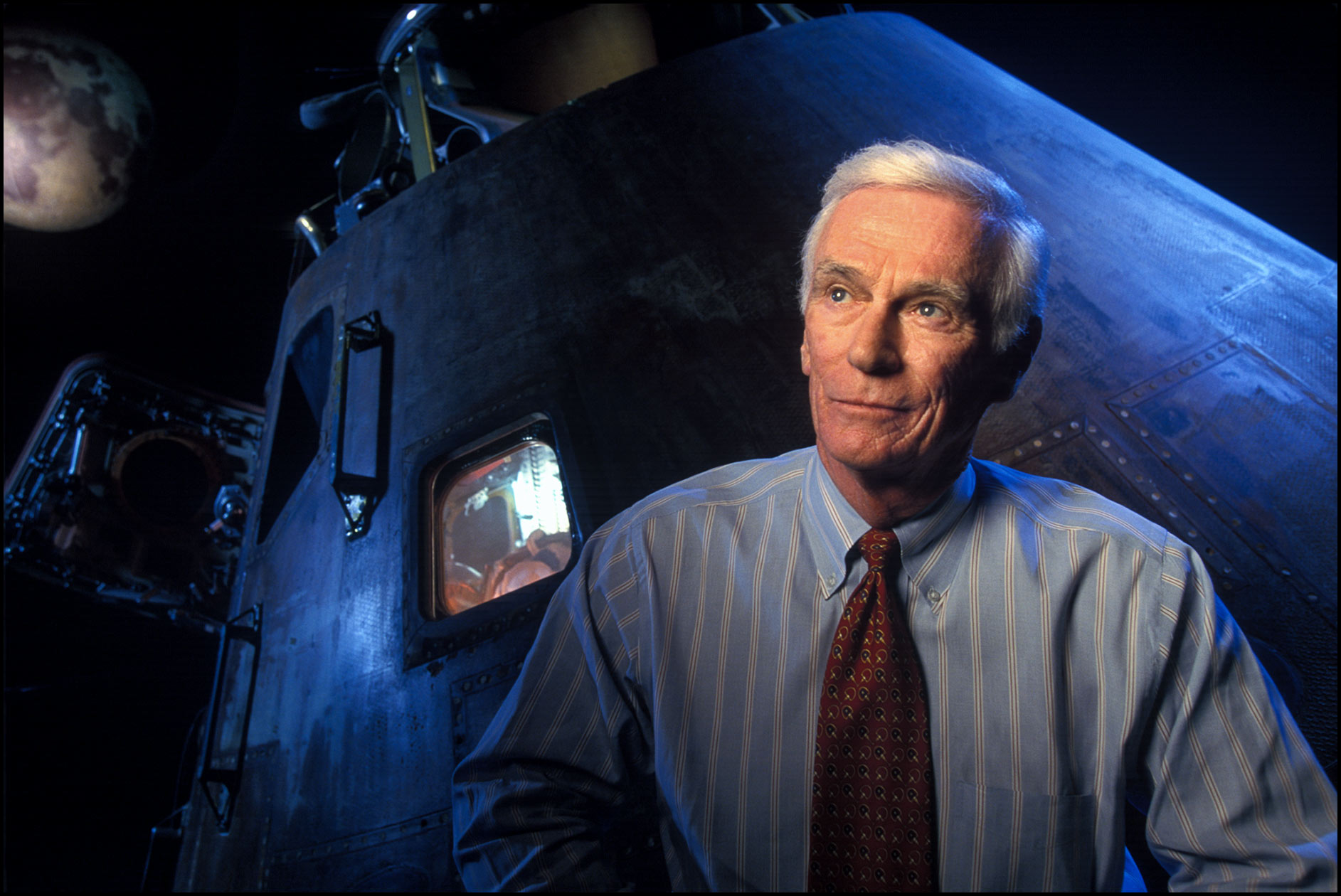 Eugene Cernan, former Apollo astronaut who walked on the moon, in front of an Apollo space capsule display.