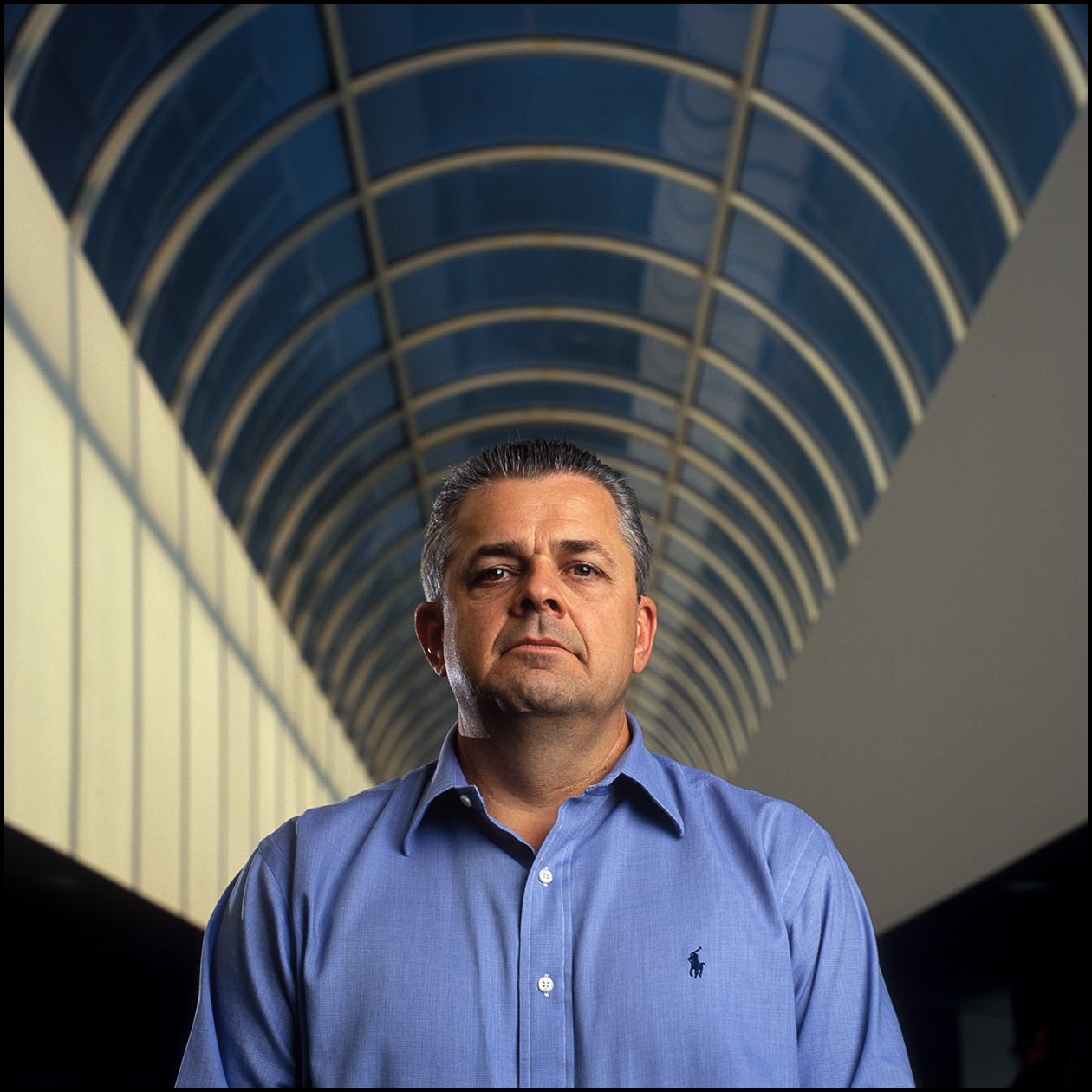 A business portrait of a CIO in a large office atrium.