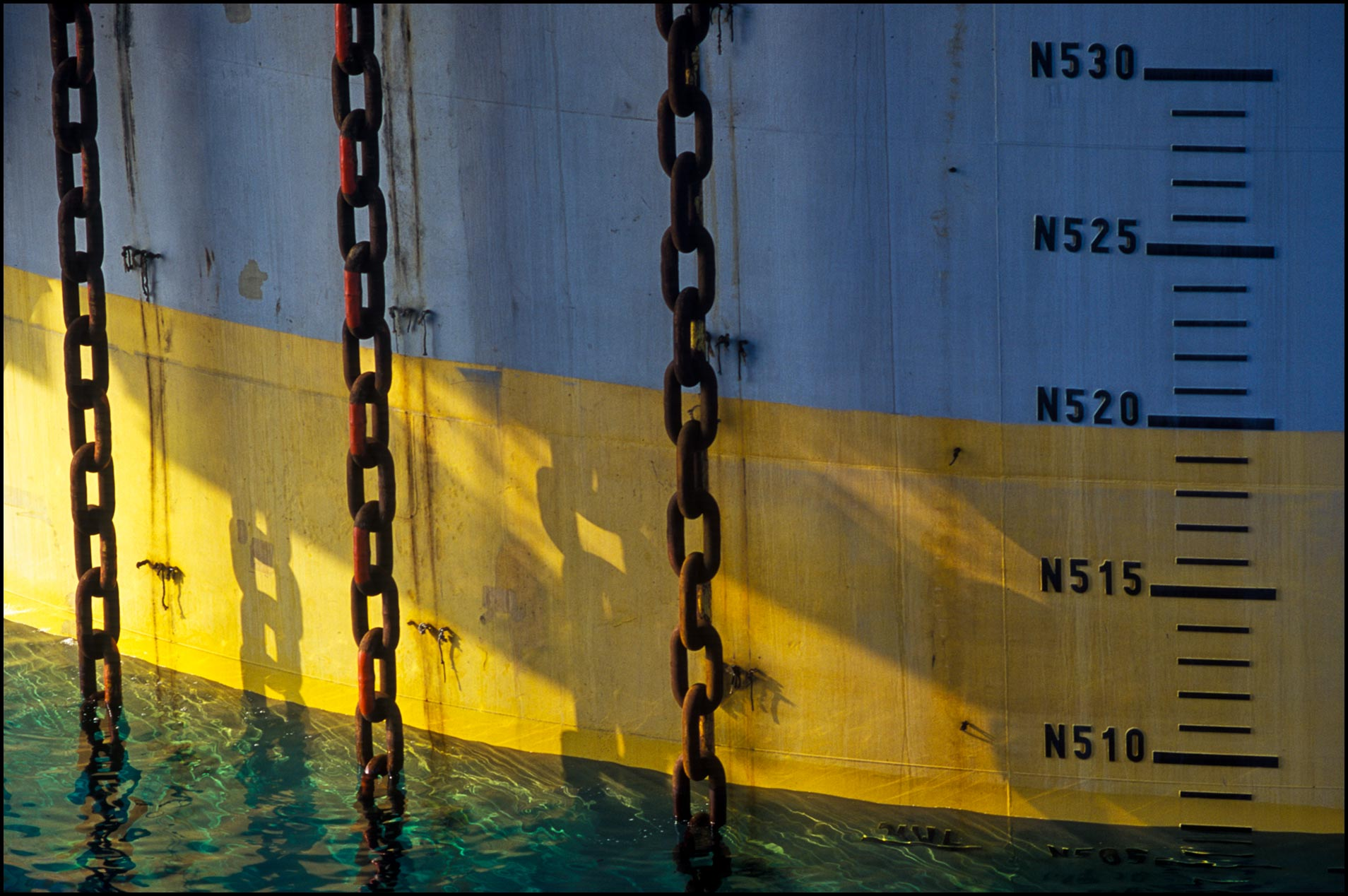 Detail of huge mooring chains fastened to ocean floor stabilize offshore rig of spar design.