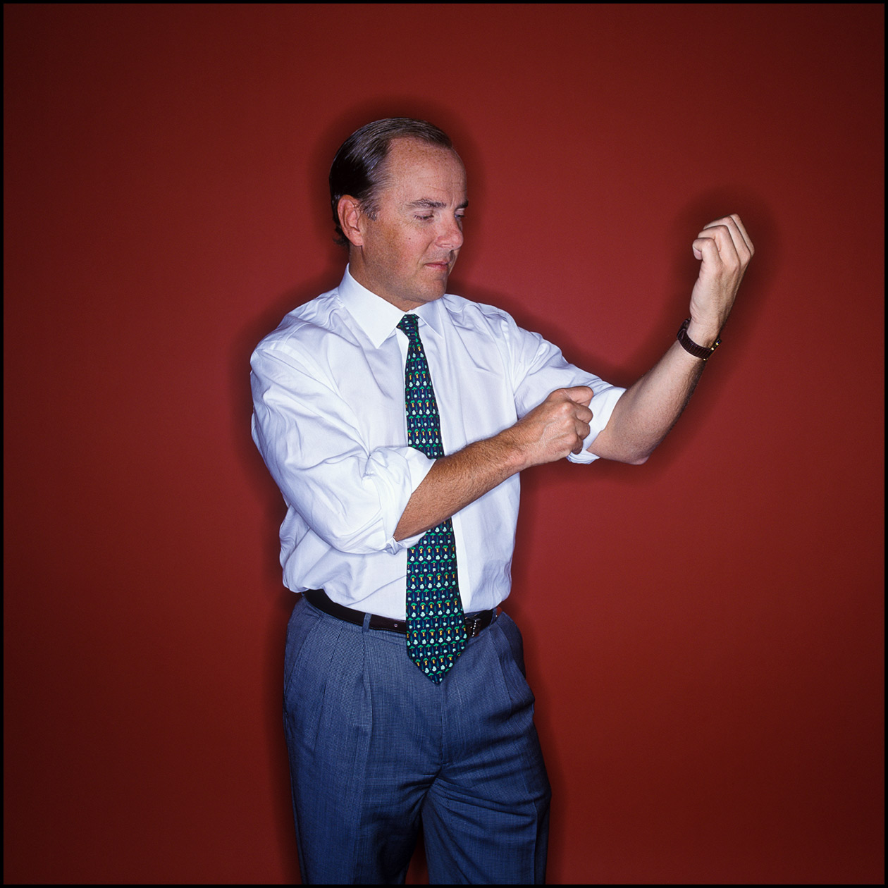 Portrait of Jeff Skilling, former Enron CEO, rolling up his sleeves in front of a red wall.