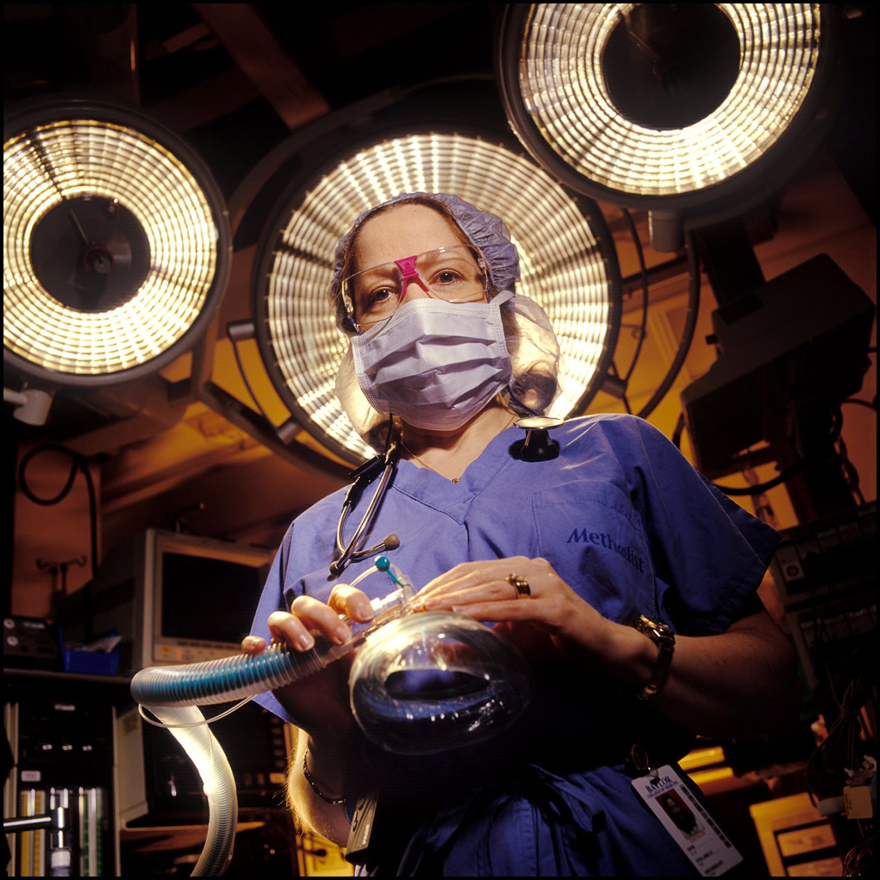 Portrait of an anesthesiologist in scrubs and face mask inside an operating room.