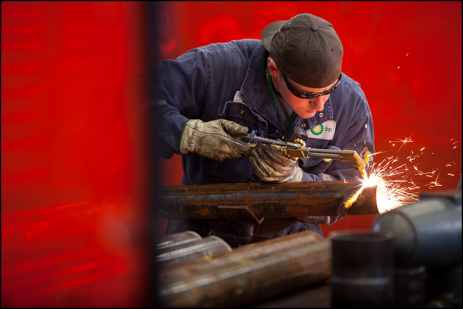 A welder uses a cutting torch behind red safety barriers in a refinery fabrication shop