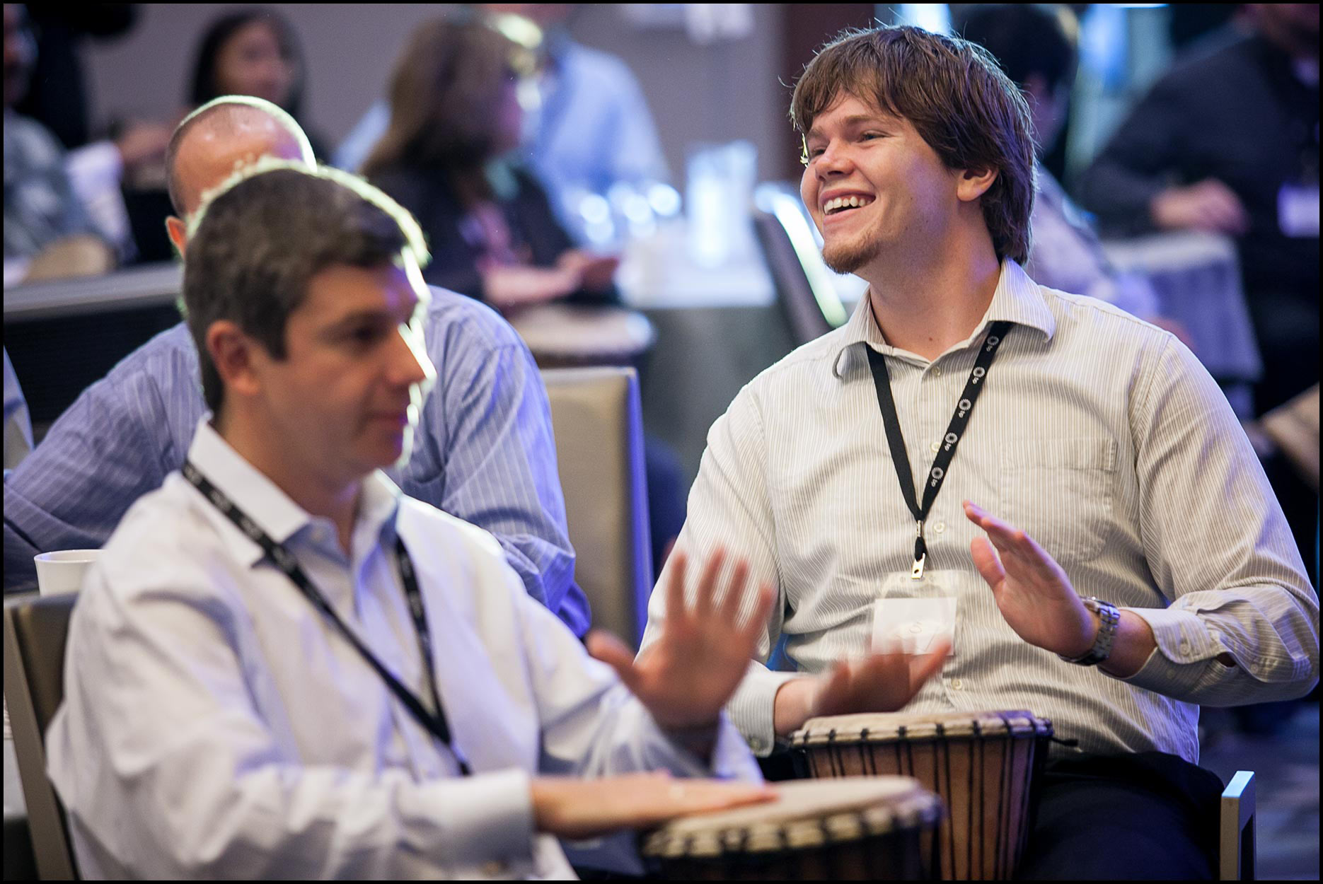 Corporate employees pound drums in a team-building exercise to begin a conference.