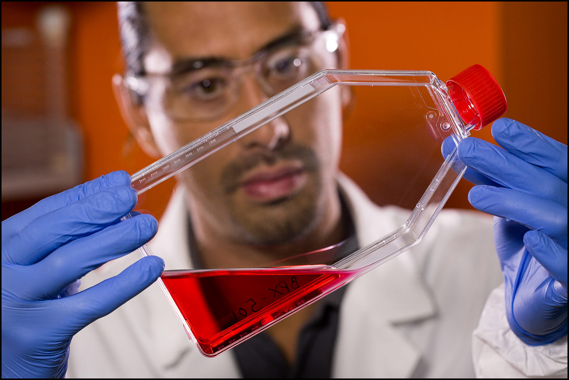 Detail of a lab technician in safety gear holding and examining a red liquid sample inside a plastic flask.