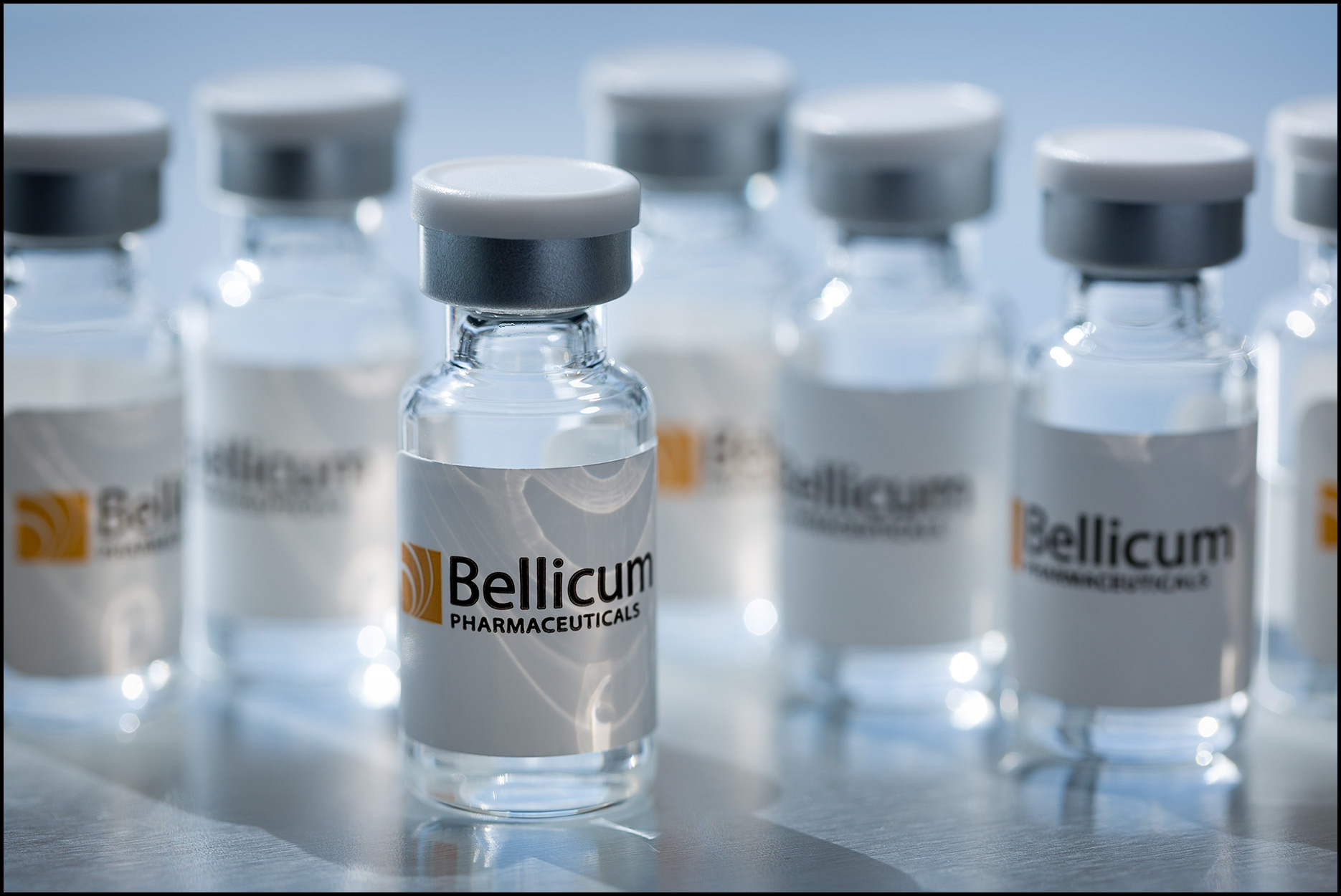 Detail of collection of small cancer drug sample vials on stainless steel surface.
