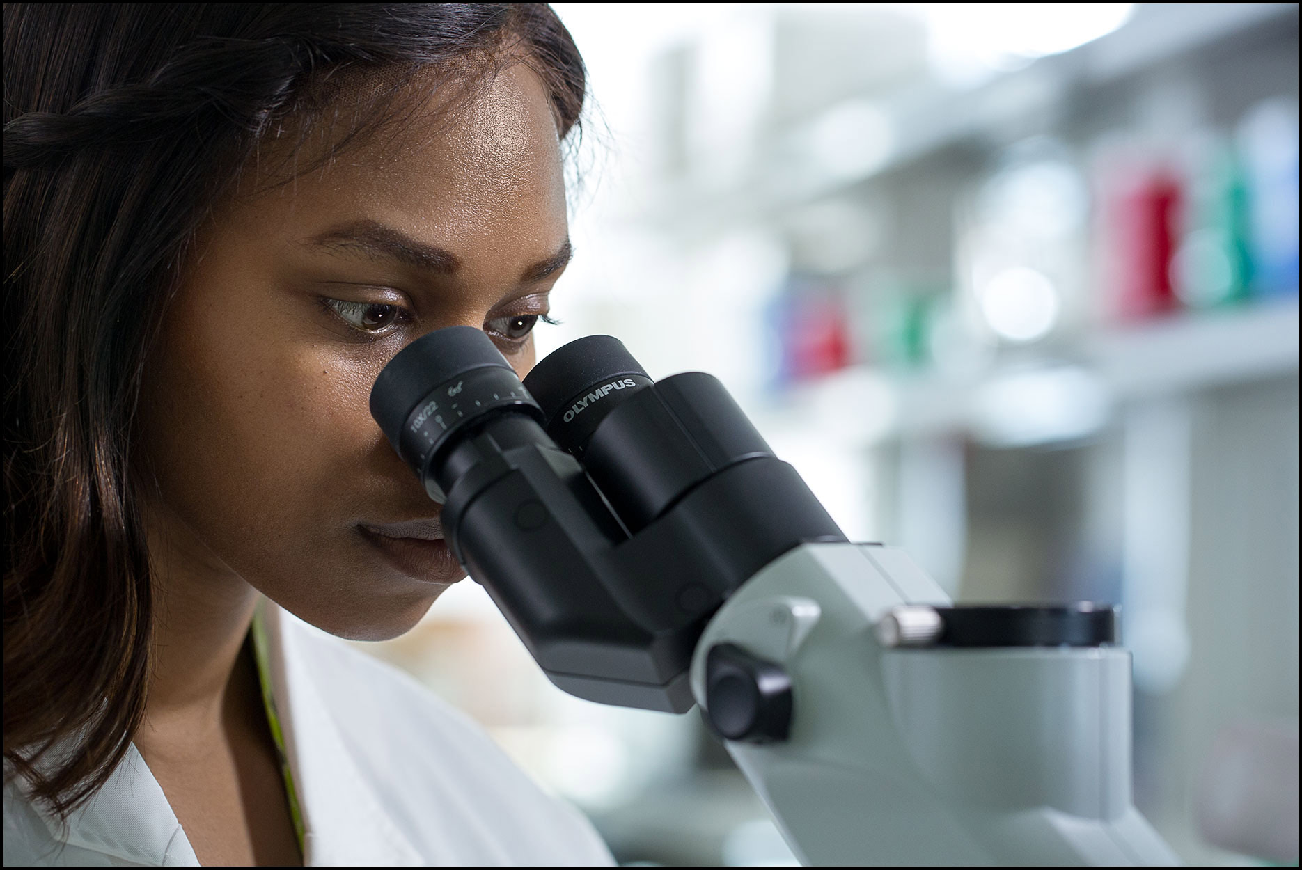 A female pharmaceutical researcher looks through a microscope inside a bright laboratory.