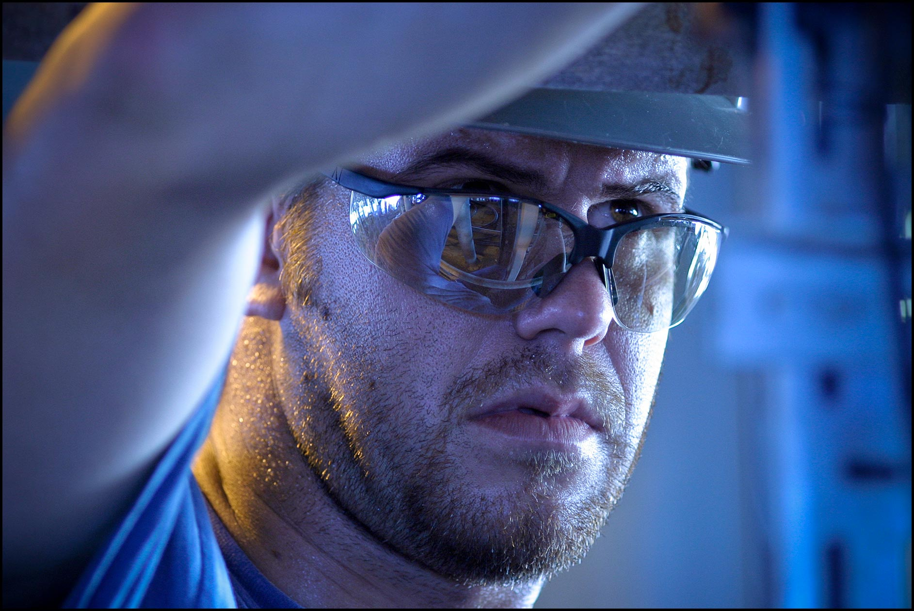 Detail of rig mechanic's face with safety glasses (PPE) looking upwards