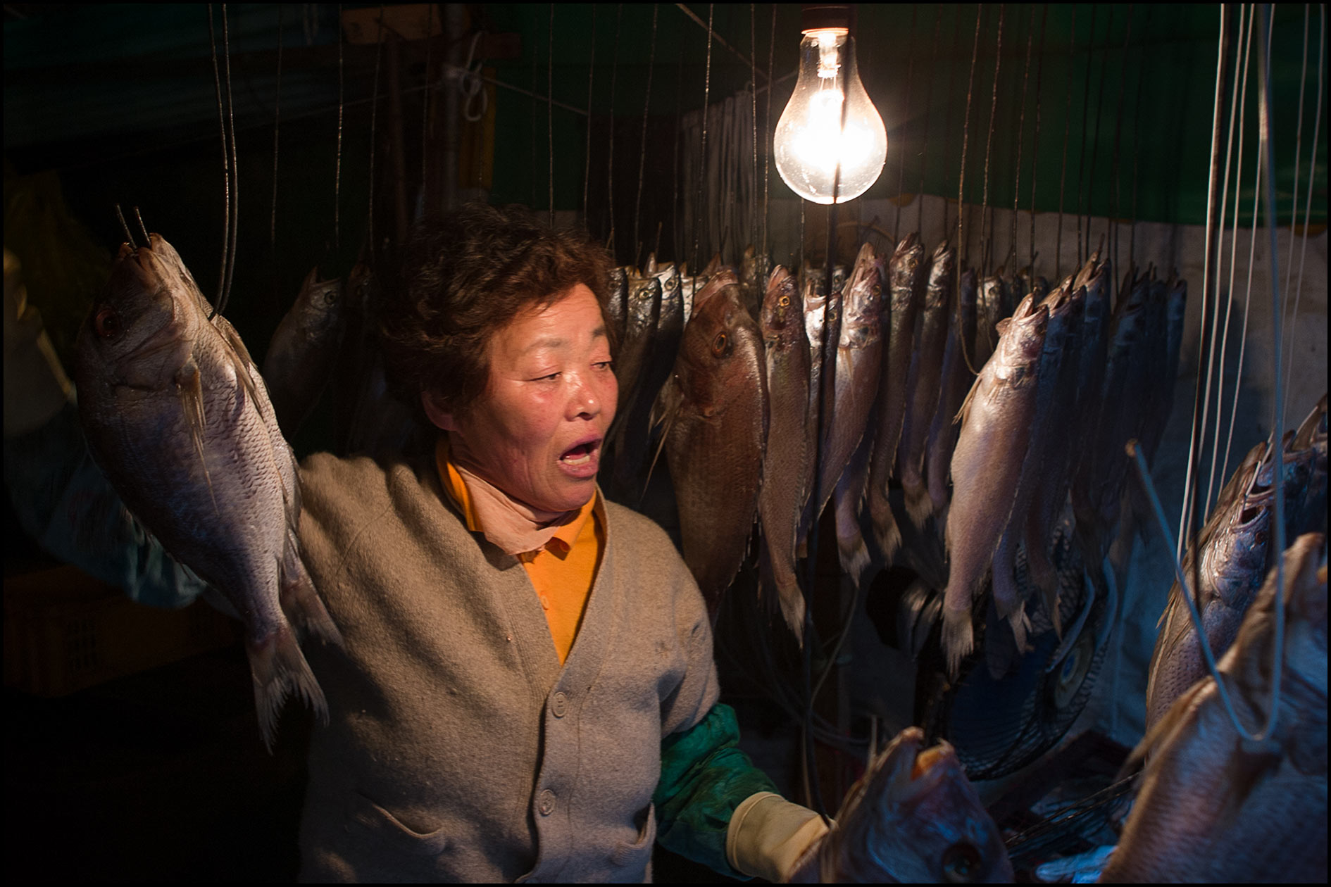 A woman handles hanging fresh fish on hooks inside a Korean market.