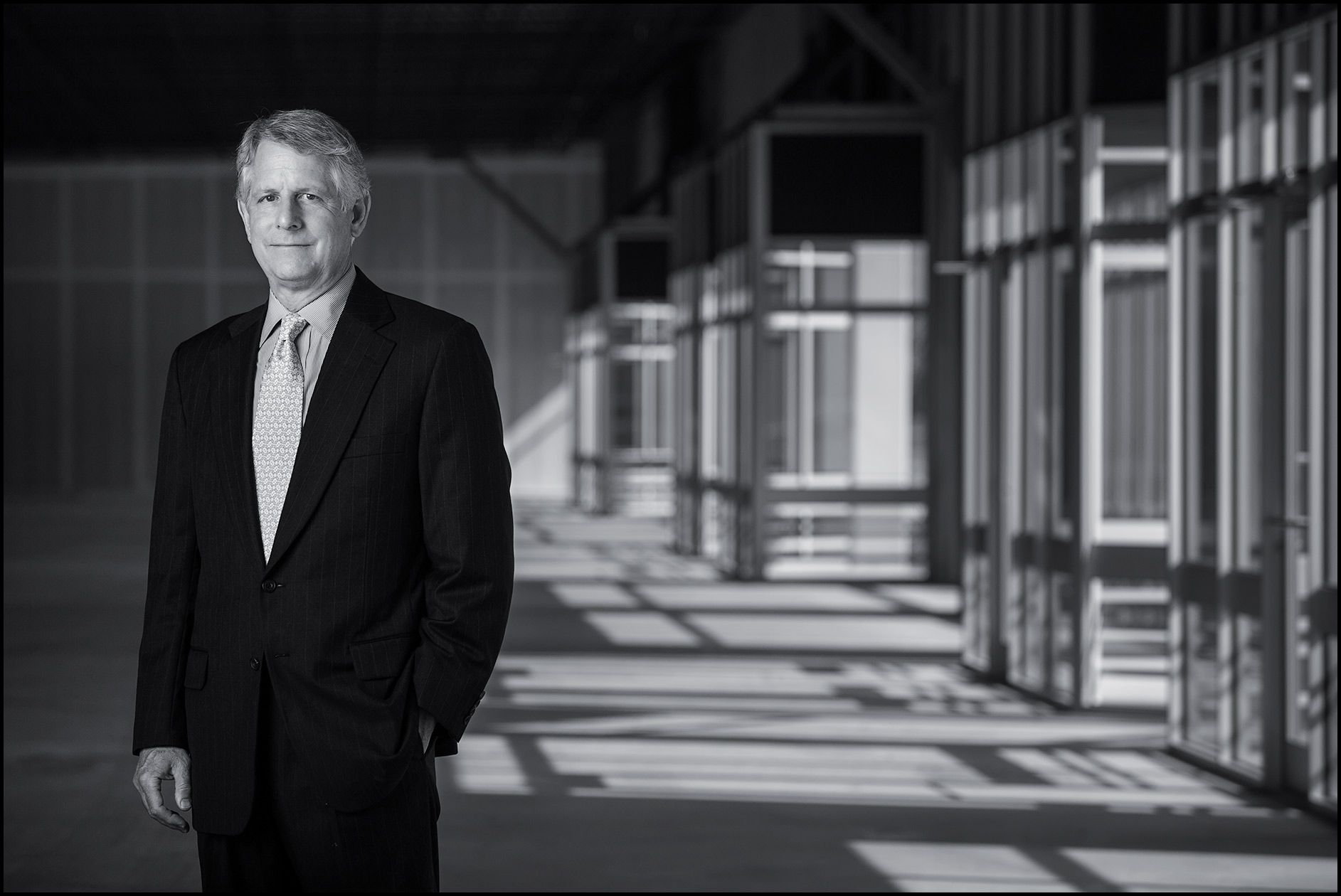 A real estate CEO stands in a vacant commercial warehouse space.