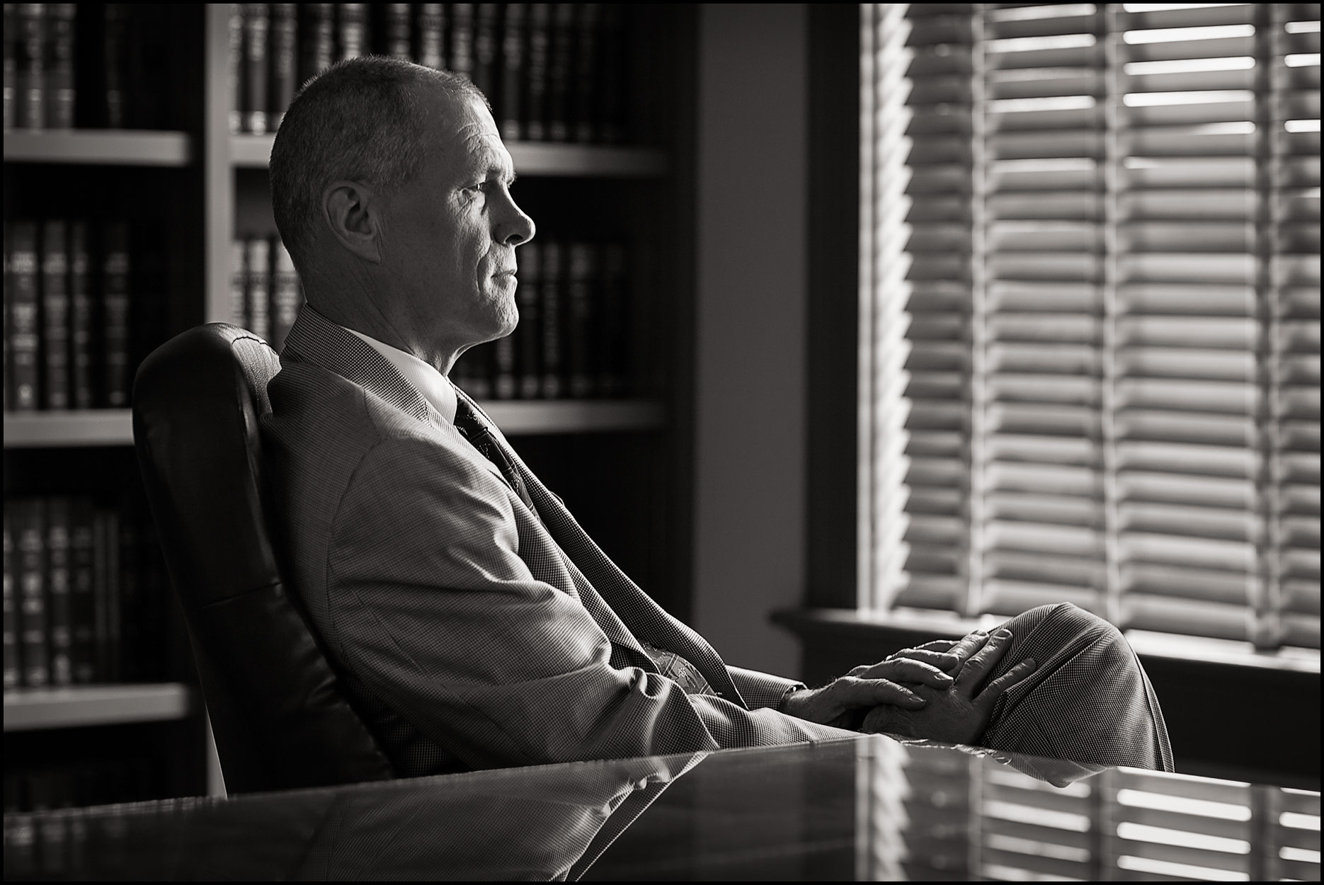 Profile portrait of an attorney in his office with blinds closed in the background.