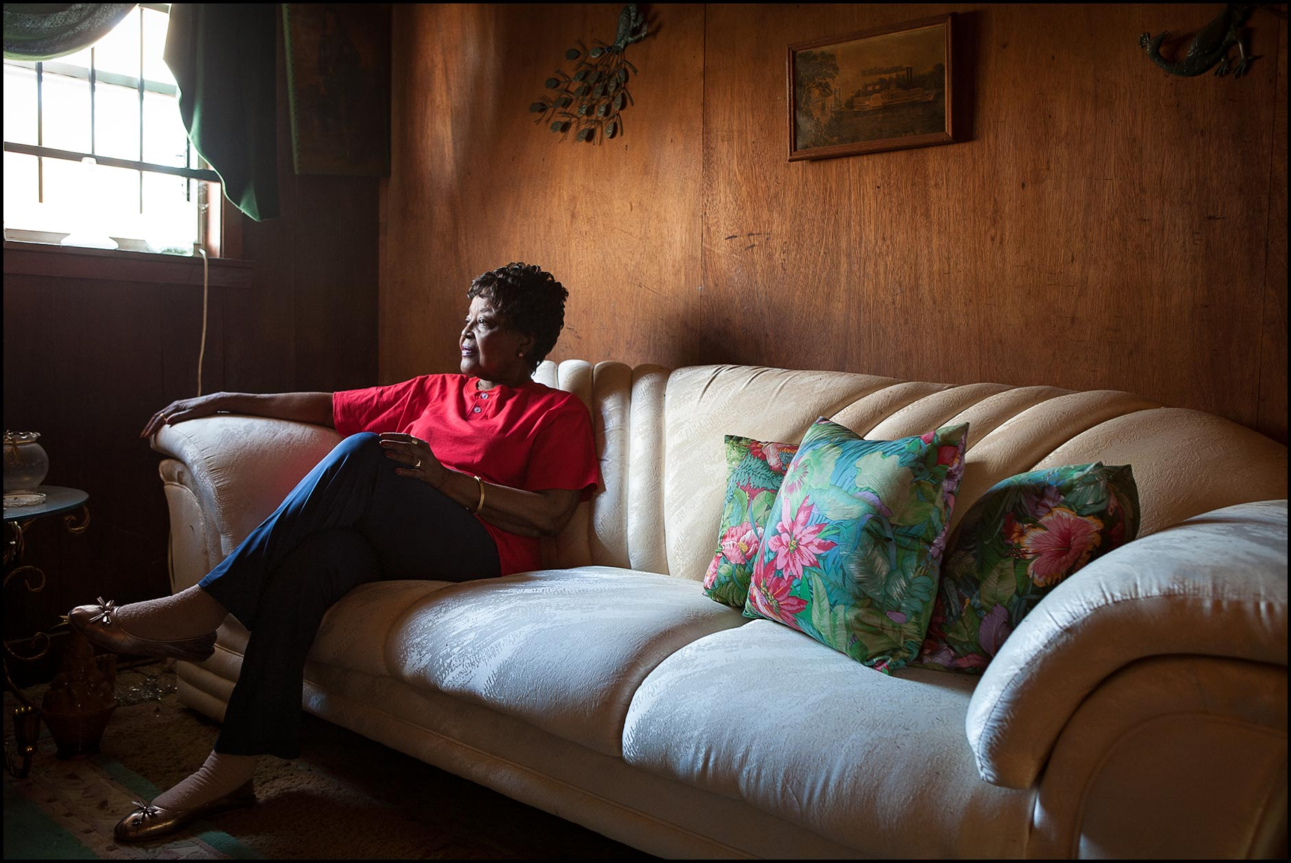 An African-American female senior citizen sits on her white sofa in her living room.