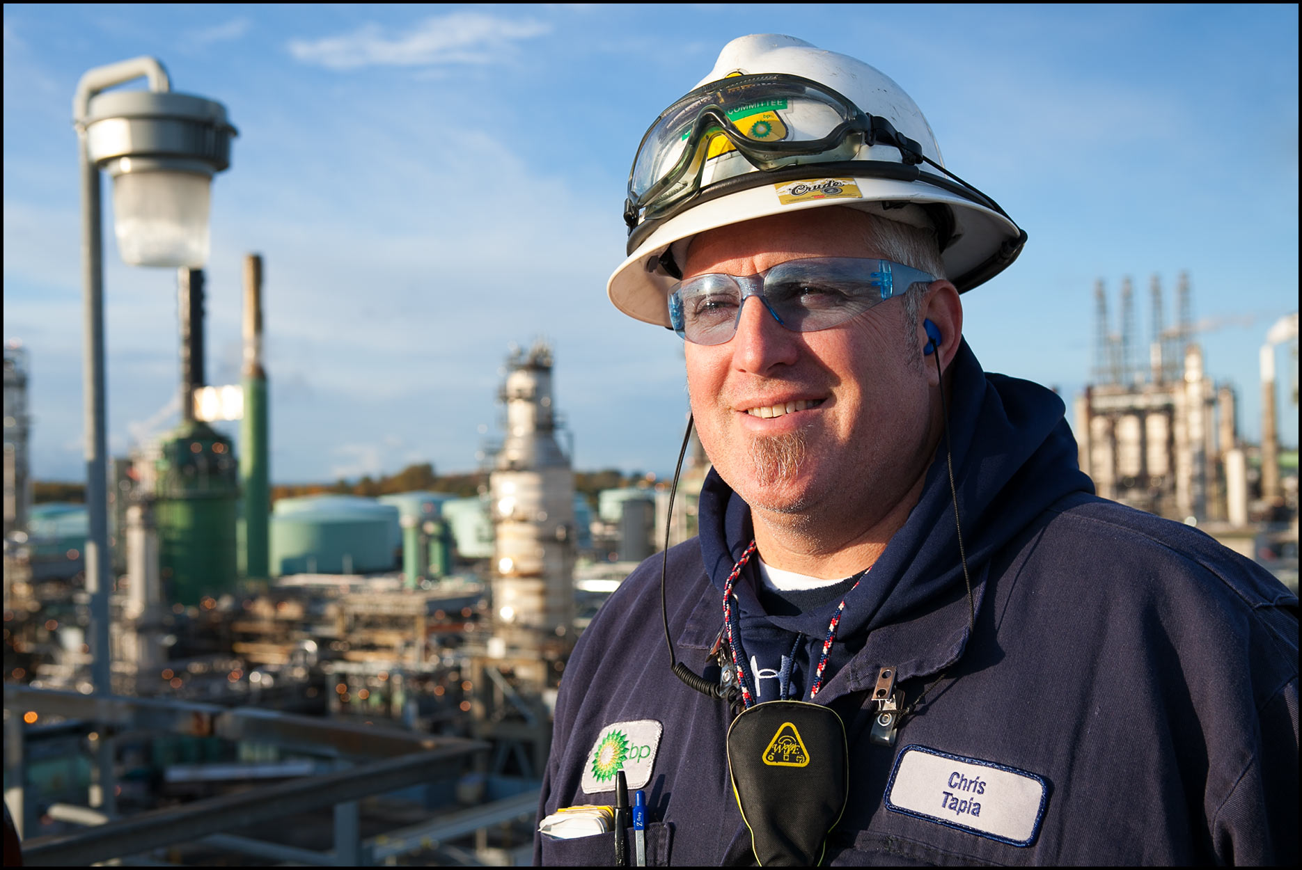 A portrait of a refinery operator wearing blue safety glasses and standing on top of a refinery unit.