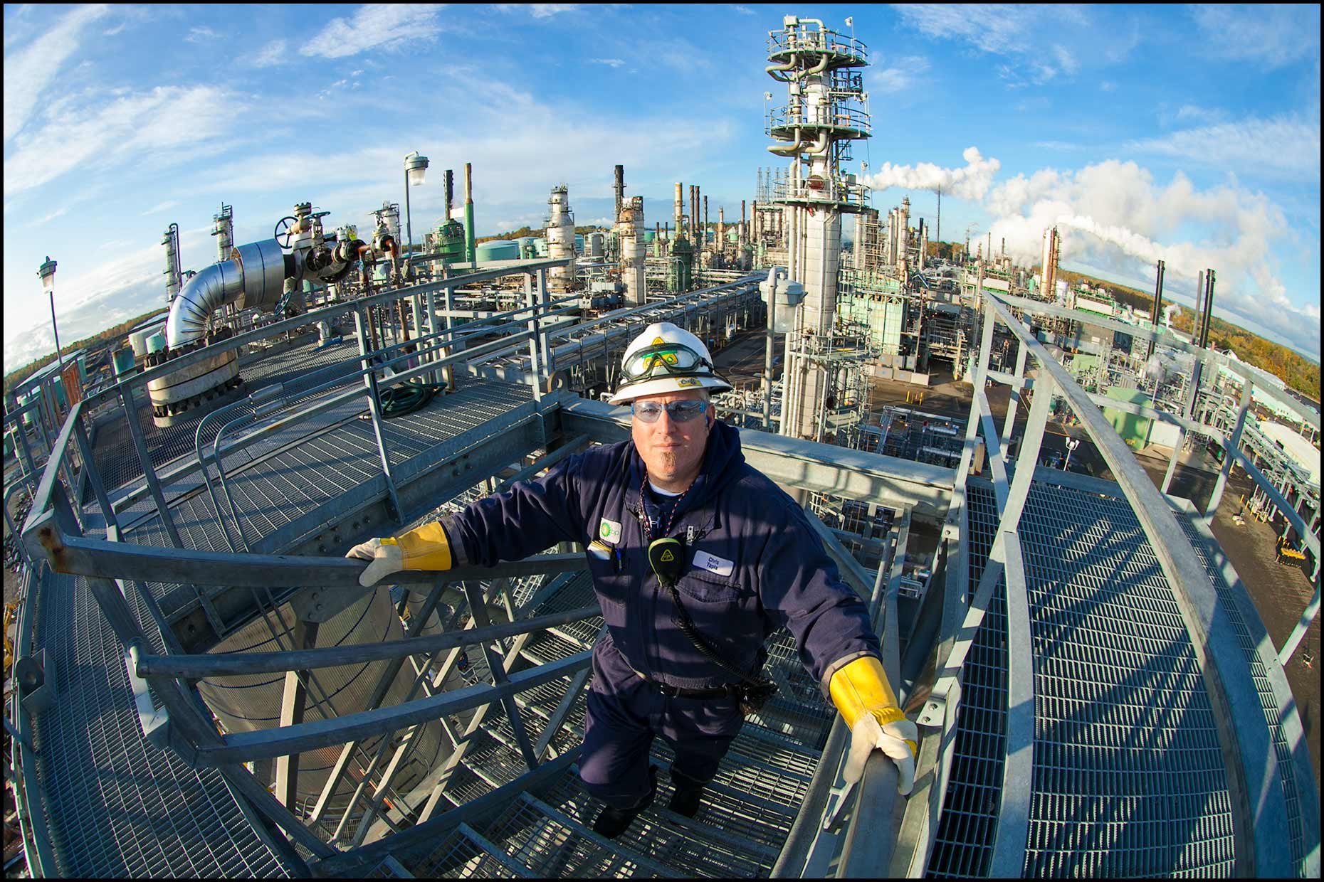 An operator on stairs at the top of a refinery unit, fisheye view.