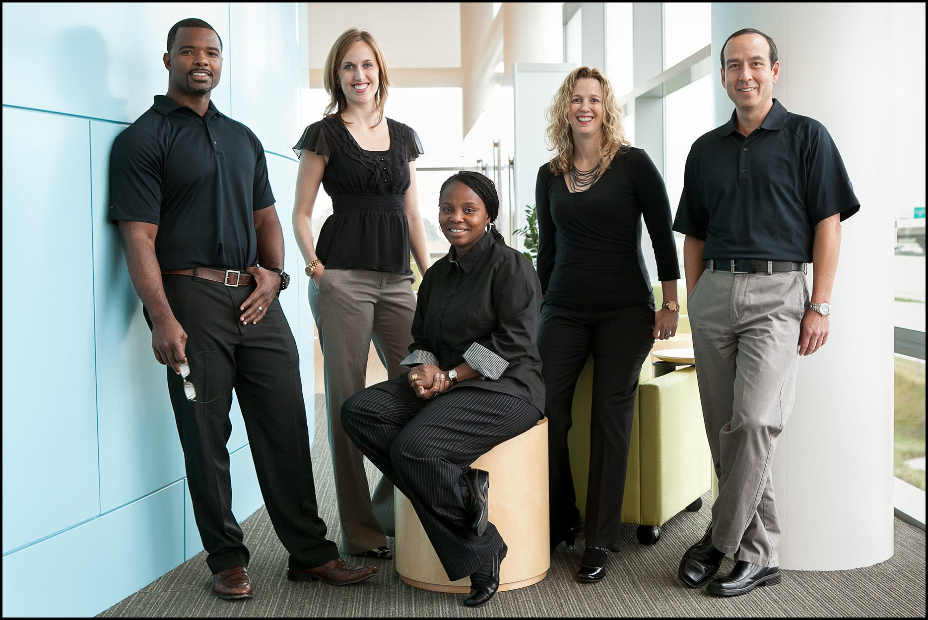 Management team, in business casual dress, stands in an office atrium for a group photo.