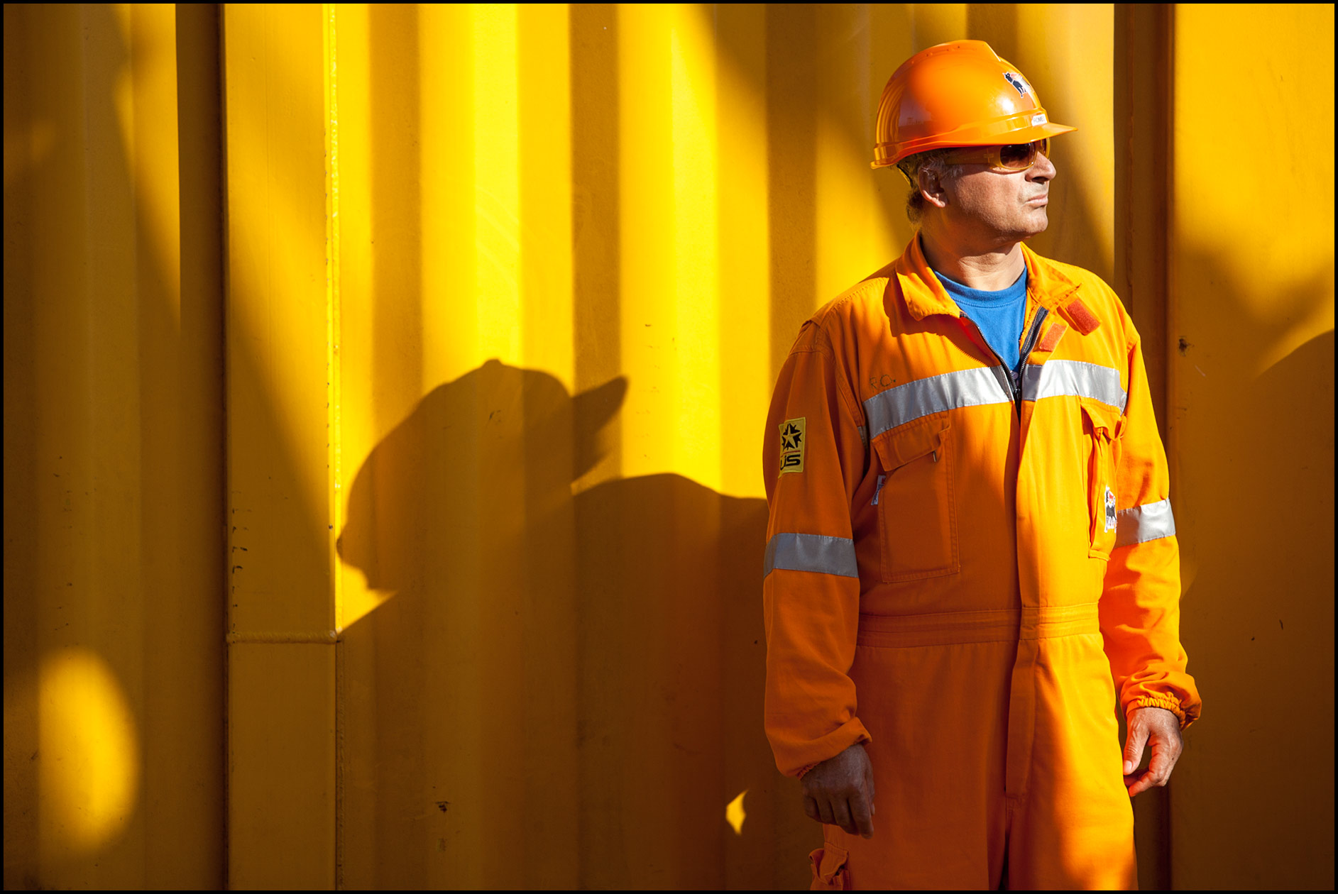 A deck worker wearing orange safety gear (PPE) stands in front of an orange wall on a deepwater construction vessel.