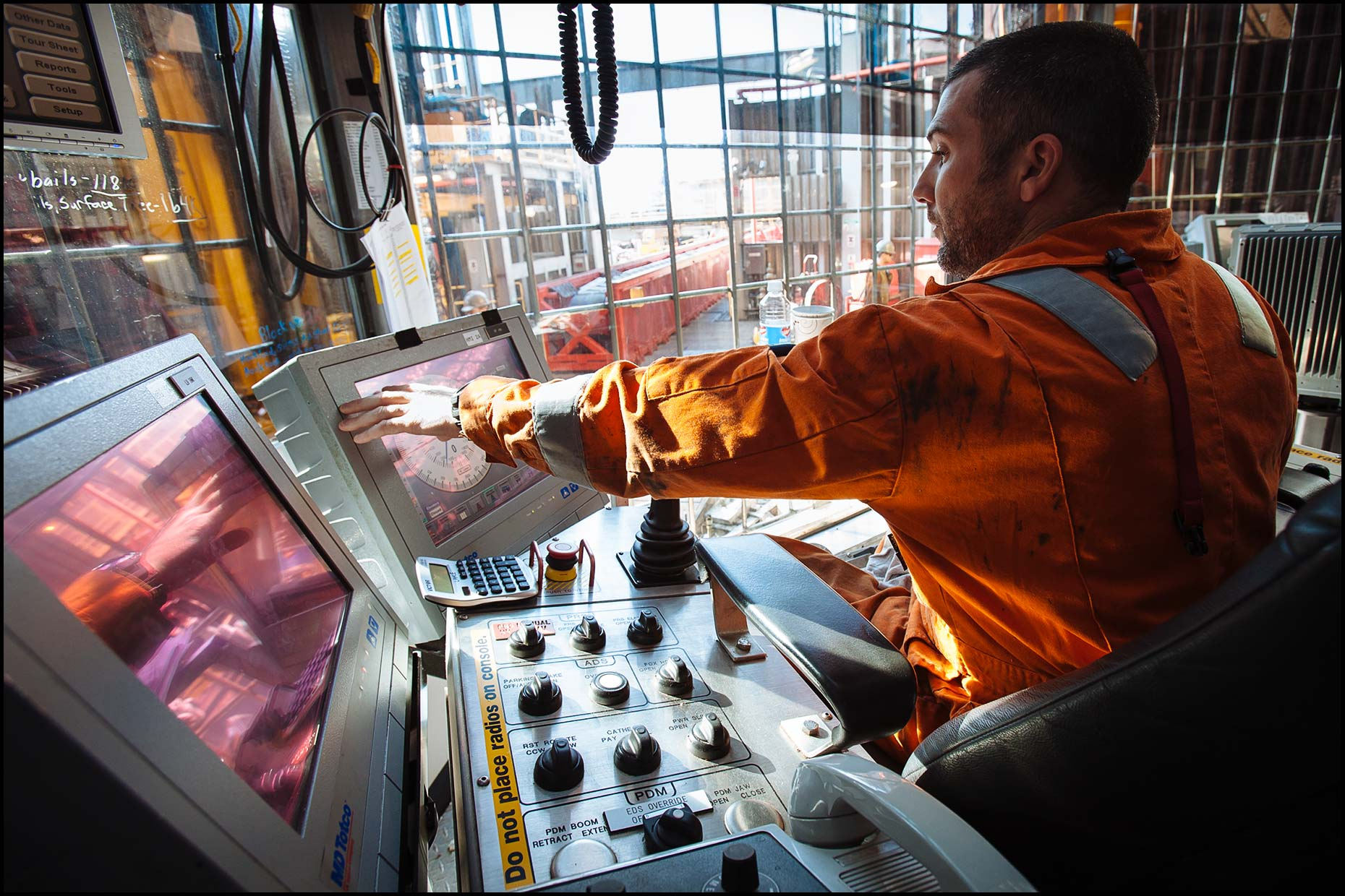 A driller operates drilling operations from inside the driller's shack (aka dog house).