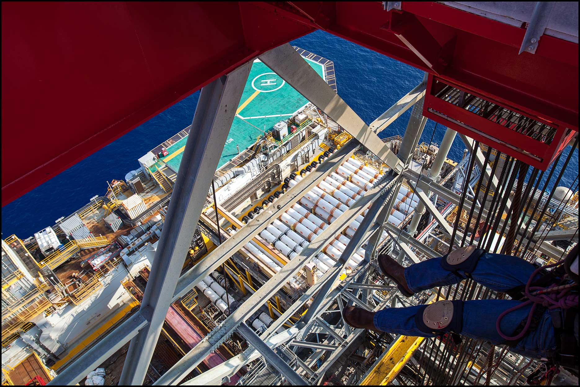An overhead view of the legs and harness of an industrial painter suspended from the underside of an offshore rig derrick, high above the deck below.