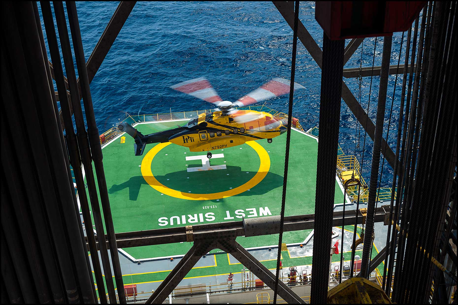 A crew helicopter lands on the helipad of an offshore drilling rig as seen through pipe stacks in the derrick.