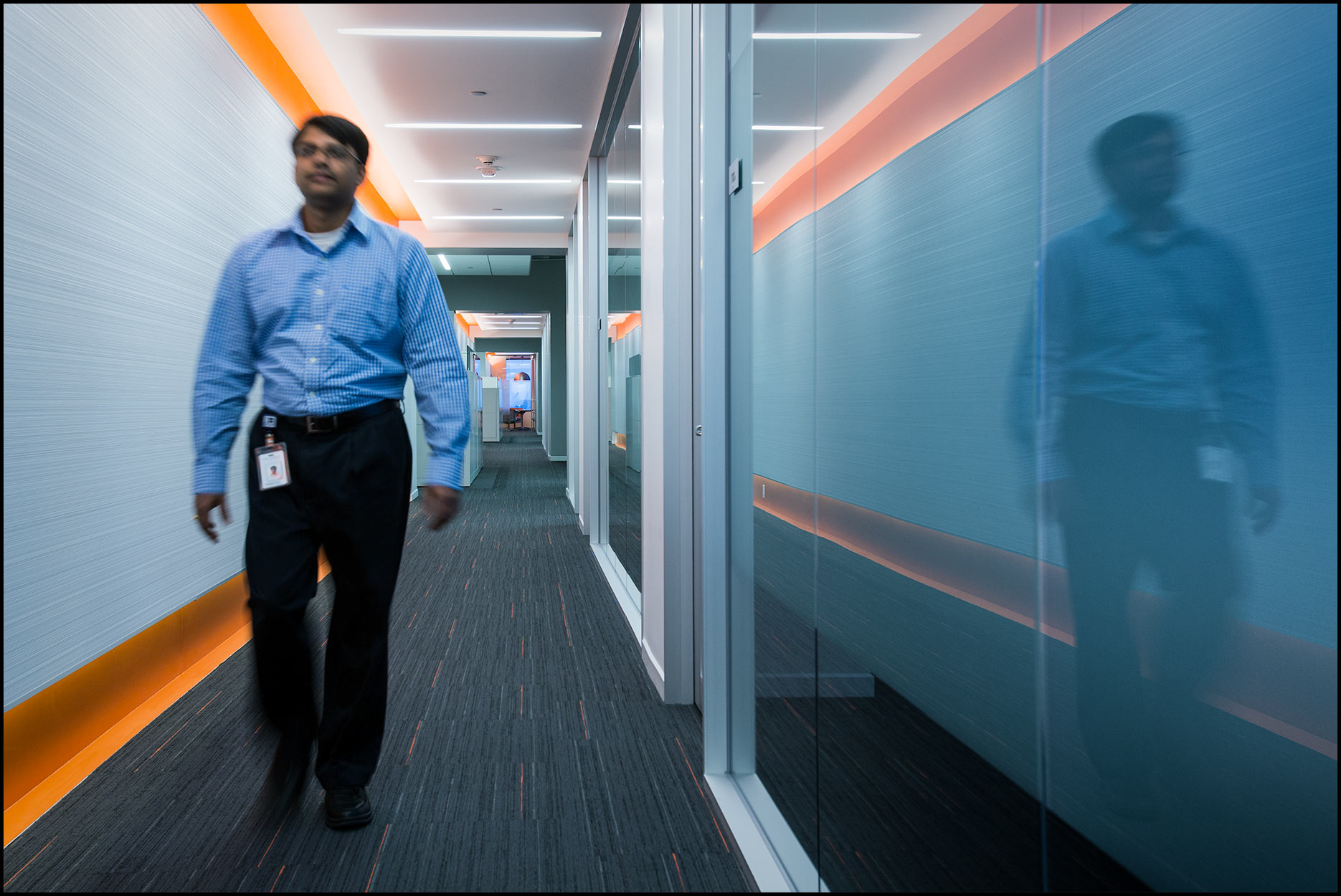 A male employee walks in a hallway with contemporary architectural decor.