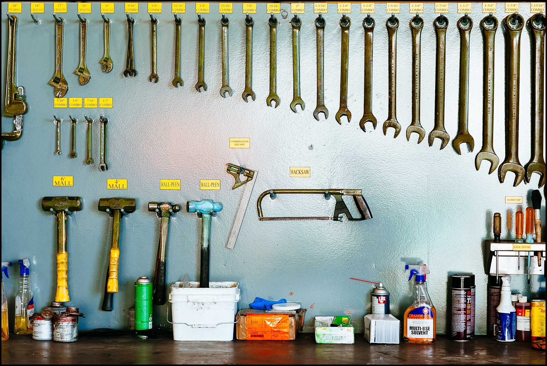 A shop tool bench has mallets, wrenches, saws, and other tools organized and labeled.