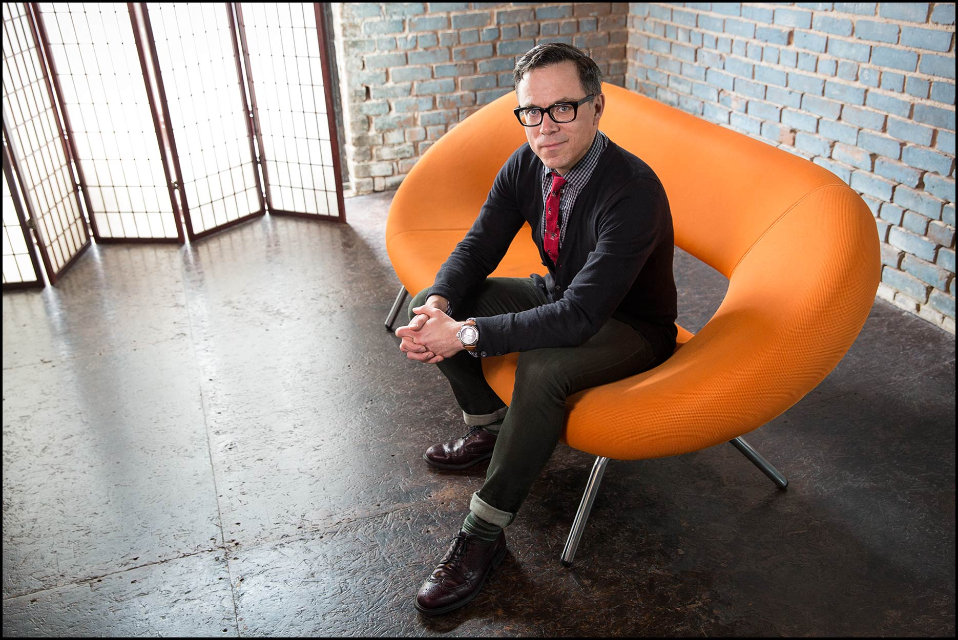 Canadian author Tim Caufield sits on an orange loveseat in front of a rustic brick wall.