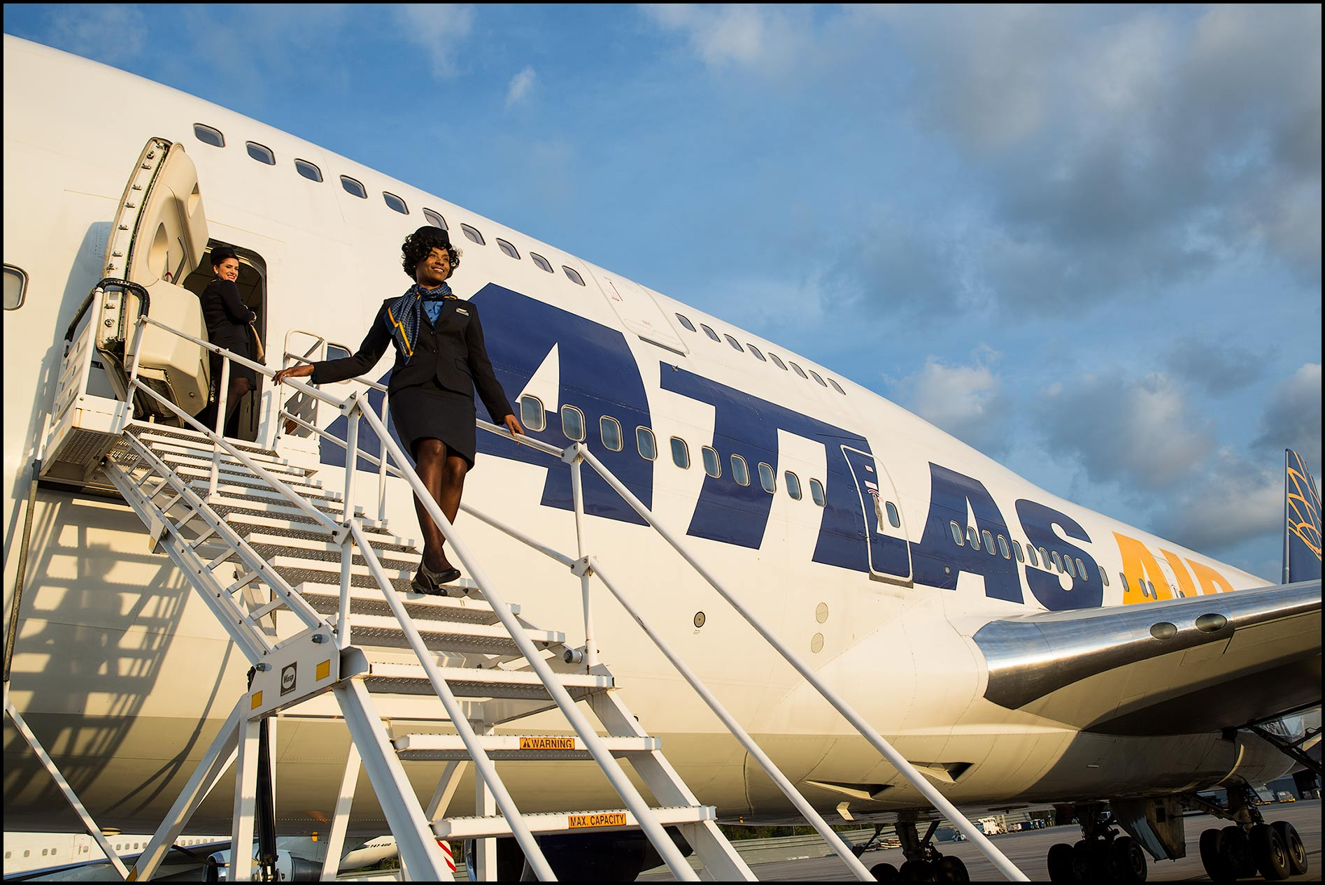 A flight attendant descends the steps of a passenger ramp of a charter jumbo jet.