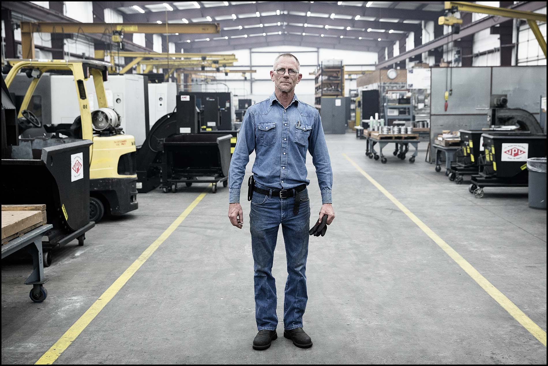 A portrait of a machinist standing in the center of a large machine shop.