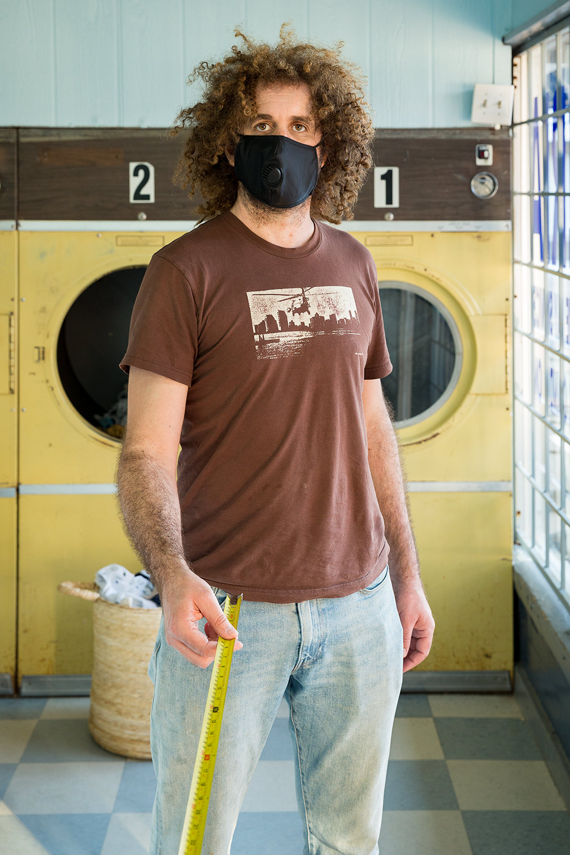 A man wearing a black mask stands inside a laundromat and holds a long tape measure that is a symbol of Covid-19 social distance