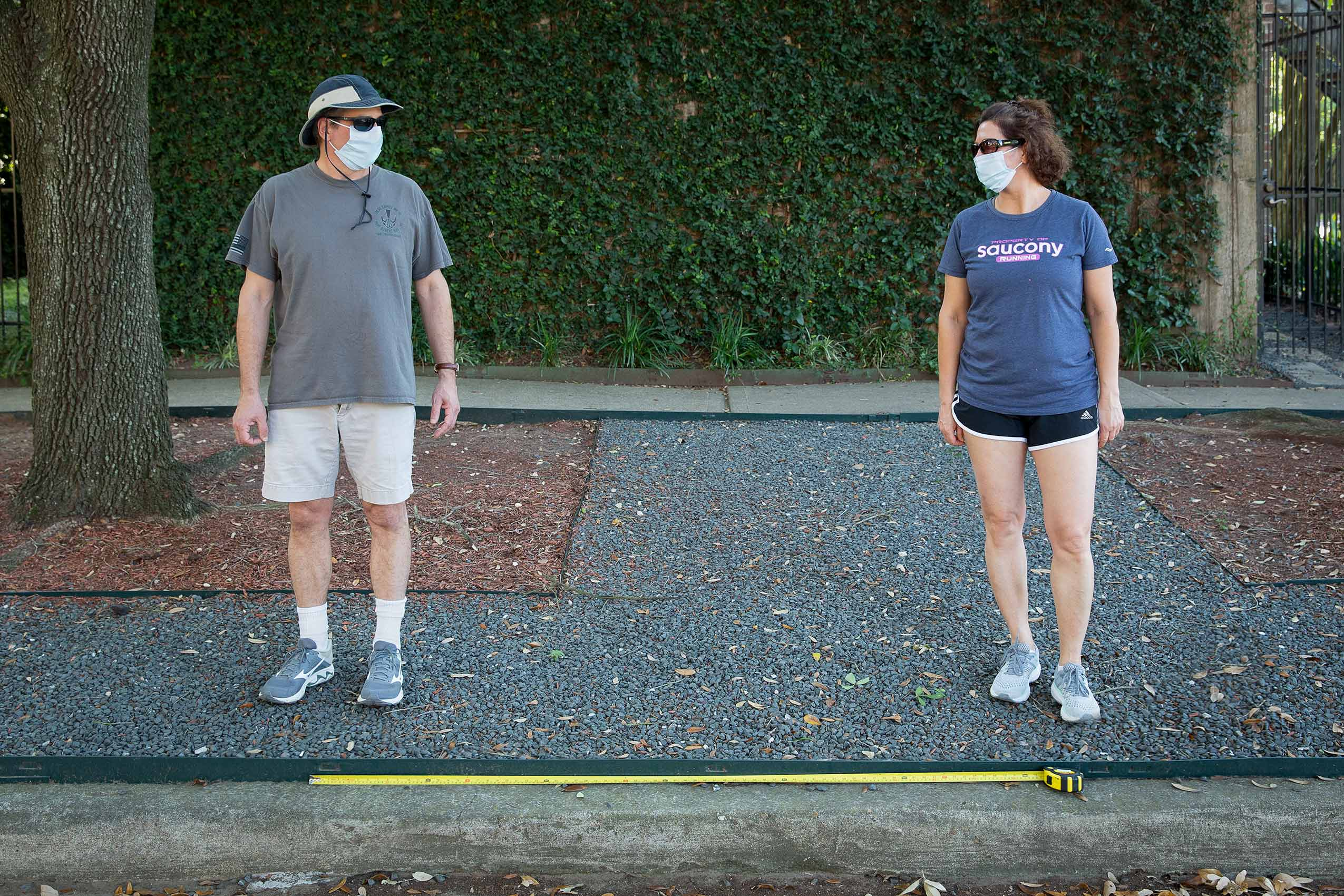 A couple wearing masks stand apart with a long tape measure as a symbol of Covid-19 social distance