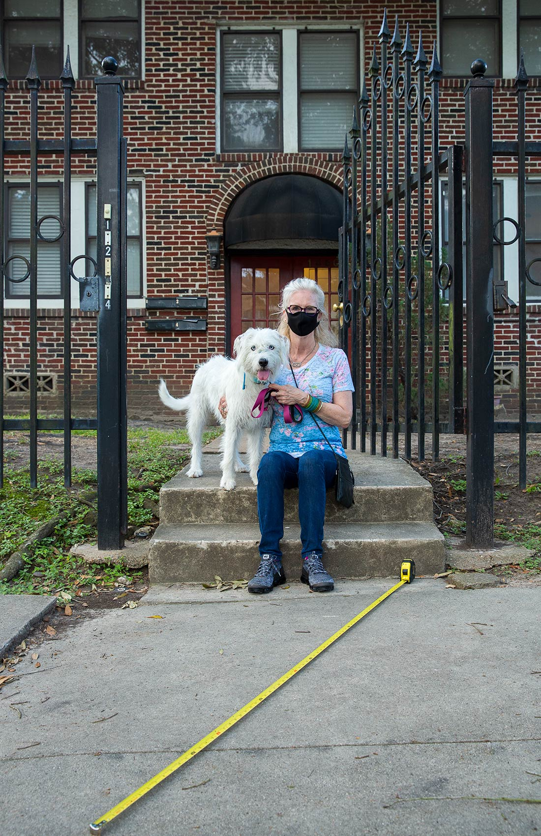 A masked woman and her dog sit on her porch with a long tape measure as a symbol of Covid-19 social distance