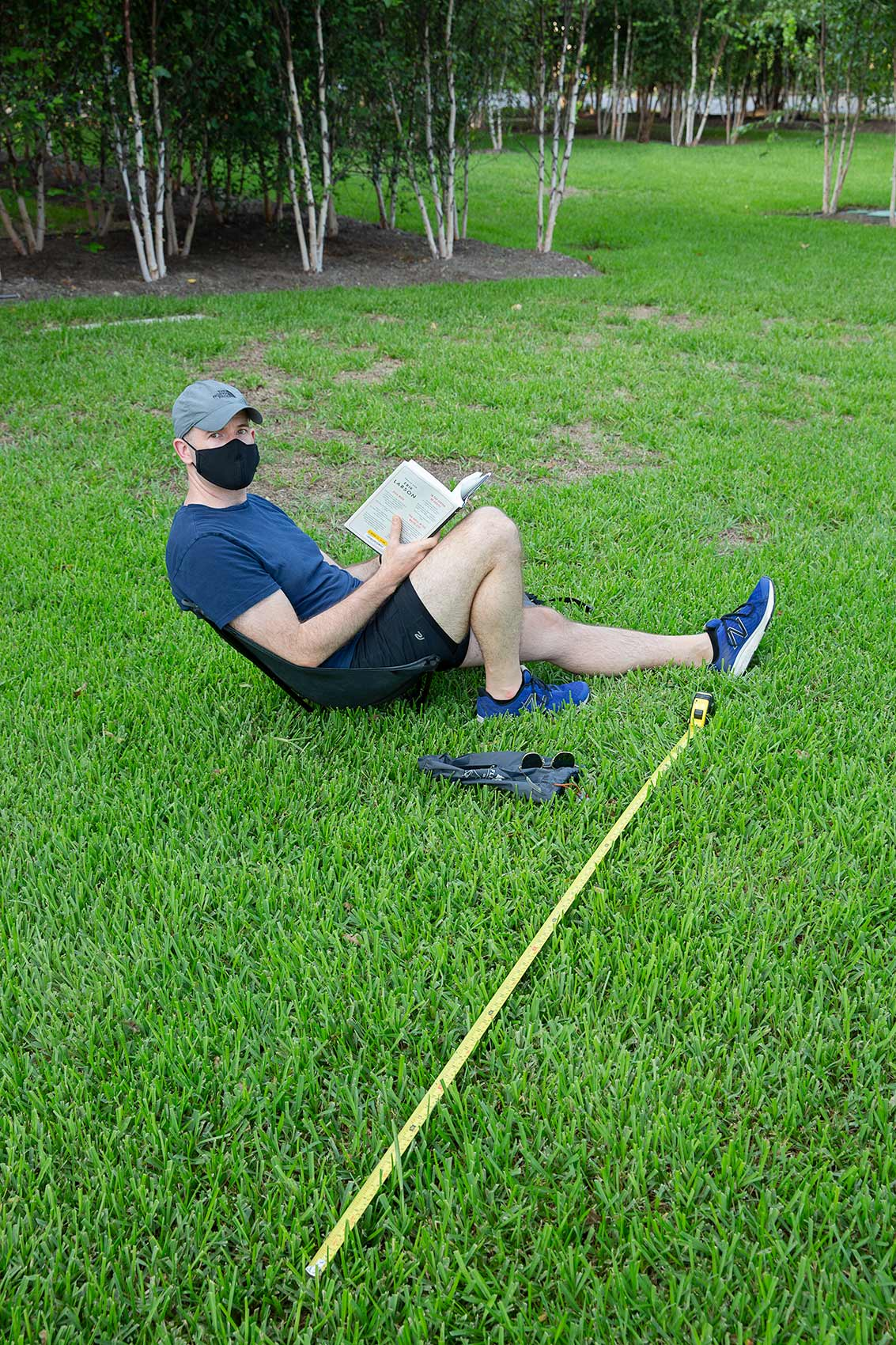 A man wearing a mask reads a book on a grassy lawn with a long tape measure as a symbol of Covic-19 social distance