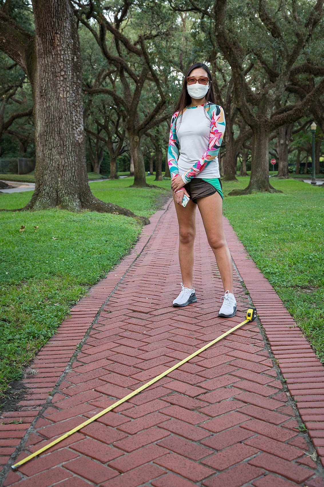 Young woman in mask on tree-lined walkway with long tape measure as a symbol of Covid-19 social distance